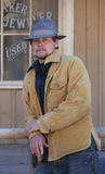 Cowboy leaning on rail. Serious young man leaning on a rail in a western scene royalty free stock photography