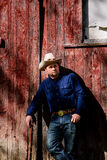 Cowboy Leaning sur la grange et sourire d'un air affecté Photographie stock libre de droits