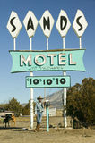 Cowboy leans against post in front of Sands Motel sign with RV Parking for $10, at the intersection of Route 54 & 380 in Carrizozo Royalty Free Stock Images