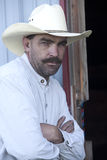 Cowboy leans on door frame. Stock Image