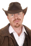 Cowboy leather coat hat smirk close. A cowboy in a hat and a vest and white shirt with a smirk on his face stock photography