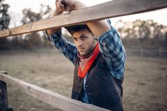 Cowboy in leather jacket and hat poses on ranch royalty free stock image