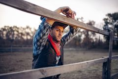 Cowboy in leather jacket and hat poses on ranch royalty free stock photography