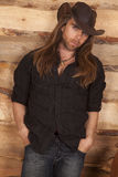 Cowboy long hair by cabin look. A cowboy leaning up against a wood wall with a serious expression on his face royalty free stock images