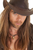 Cowboy long hair close serious. A cowboy with a serious expression and hat royalty free stock image