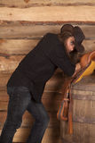 Cowboy long hair lean on saddle on barrel Stock Photo