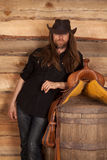Cowboy long hair stand by saddle on barrel Royalty Free Stock Image