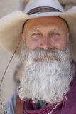 Cowboy With a Long White Beard. Portrait of an older man with a long white beard and cowboy hat smiling towards the camera. Vertical shot Stock Images