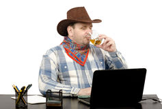 Cowboy looking news online and drinking whiskey Stock Photo