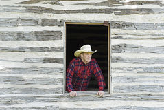 Cowboy Looking Out a Window. Handsome cowboy or rancher looking off into the distance from a rustic window Stock Images