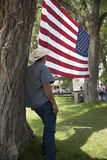 Cowboy looks at American flag stock photography