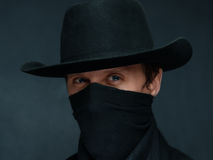 Cowboy looks at you. Portrait of a man cowboy with a scarf on his face and in a black hat royalty free stock images