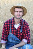 Cowboy man handsome and good looking with hat, overalls and plaid shirt in rural USA countryside. Male model in american western. Prairie landscape nature on Stock Images