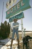 Cowboy med hundställningen framme av sandmotelltecknet med RV-parkering för $10 som lokaliseras på genomskärningen av rutt 54 & 3 Royaltyfri Foto
