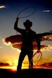 Cowboy met kabel in luchtzonsondergang stock foto