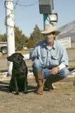 Cowboy met zijn hond stock fotografie