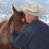 A cowboy needs a horse. A cowboy hugs his horse Royalty Free Stock Photo