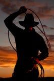 Cowboy nel tramonto con la corda Immagini Stock Libere da Diritti