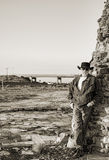 Cowboy next to a highway leaning against an old stone chimney Royalty Free Stock Photo