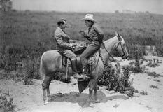 Cowboy och affärsman som spelar kontrollörer på hästrygg (alla visade personer inte är längre uppehälle, och inget gods finns Lev fotografering för bildbyråer