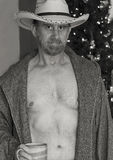 A Cowboy in an Open Robe by a Christmas Tree Stock Images