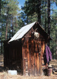Cowboy Outhouse. Cowboy hat hangs above a rural outhouse stock images