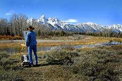 Cowboy painting teton mountains. Cowboy artists painting teton mountain range on easel Stock Images