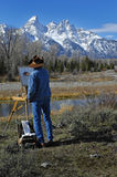 Cowboy painting teton mountains. Cowboy artists painting teton mountain range on easel Royalty Free Stock Photography
