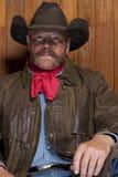 Cowboy par un mur en bois Image stock