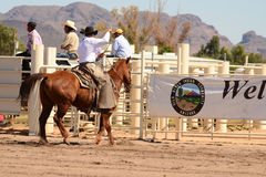 Cowboy participates in bucking horse competition. Sacaton, Arizona United States, March 16, 2014: Mul-Chu-Tha Rodeo contestants - Bucking horse Bronc busting Royalty Free Stock Photos
