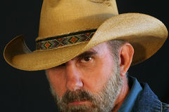 A Cowboy Peers with One Eye. A Bearded Cowboy Against Black Peers with One Eye Stock Images