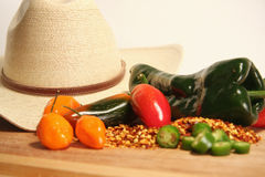 Cowboy Peppers. Cowboy Hat with an assortment of hot peppers on a cutting board Stock Image