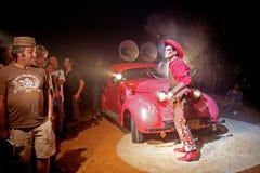 Cowboy perto de um carro vermelho Imagem de Stock