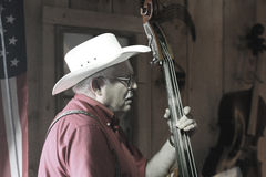 Cowboy plays bass instrument Royalty Free Stock Photography