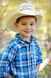 Cowboy. A portrait of a young five year old boy dressed like a cowboy and posing in front of a fall forest with yellow leaves.  He is wearing a blue plaid shirt Stock Photos