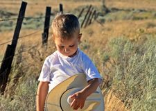 COWBOY PRAYER. Young boy standing in a field of sagebrush in front of a barbed wire fence holding his cowboy hat Stock Photos