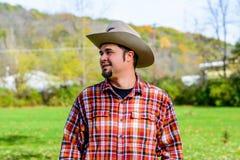 Cowboy Rancher Looking zum mit Seiten zu versehen und Lächeln Stockbild