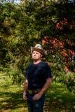 Cowboy Rancher vor Kiefer Stockbild