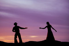 Cowboy reach for woman silhouette Stock Photos
