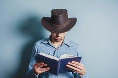 Cowboy reading a book Stock Photos