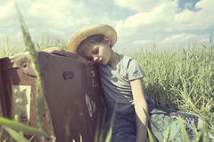 Young cowboy relaxes over his heavy suitcase in a meadow. Cowboy relaxes over his heavy suitcase in a meadow Stock Image