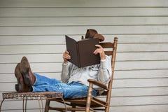 Cowboy Relaxing op Portiek in Schommelstoel stock afbeeldingen