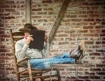 Cowboy Relaxing på den lantliga farstubron i gungstol arkivbild