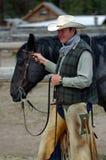 Cowboy retenant le cheval Roan bleu Images stock