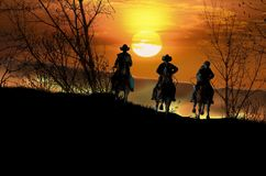 Cowboy riders at sunset. Three cowboys on their horses, riding at sunset by hills and fields Stock Image