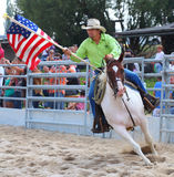 Cowboy riding with American flag. Stock Images