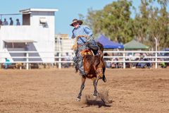 BOWEN RIVER, QUEENSLAND, AUSTRALIA - JUNE 10TH 2018: Cowboy competing in the Saddle Bronc event at Bowen River country rodeo. A cowboy riding a bucking bronco at royalty free stock images