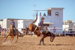 BOWEN RIVER, QUEENSLAND, AUSTRALIA - JUNE 10TH 2018: Cowboy competing in the Saddle Bronc event at Bowen River country rodeo. A cowboy riding a bucking bronco stock photo