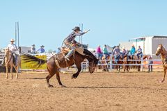 BOWEN RIVER, QUEENSLAND, AUSTRALIA - JUNE 10TH 2018: Cowboy competing in the Saddle Bronc event at Bowen River country rodeo. Cowboy riding a bucking bronco royalty free stock photo