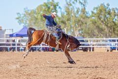 BOWEN RIVER, QUEENSLAND, AUSTRALIA - JUNE 10TH 2018: Cowboy competing in the Saddle Bronc event at Bowen River country rodeo. Cowboy riding a bucking bronco royalty free stock photos